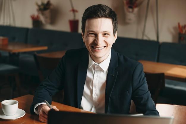 Portret van een positieve jonge blanke freelancer die in een coffeeshop werkt en gekleed in pak kijkt naar camera glimlachen.