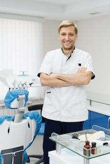Portret van een positieve jonge mannelijke tandarts in uniform met gekruiste handen bij de tandartspraktijk