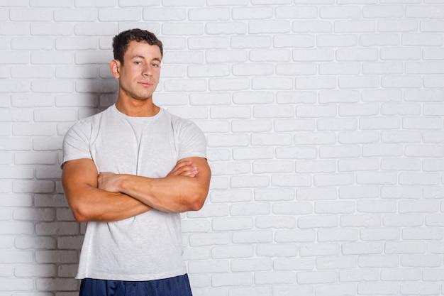 Portret van een positieve jonge mens die zich tegen witte bakstenen muur bevindt