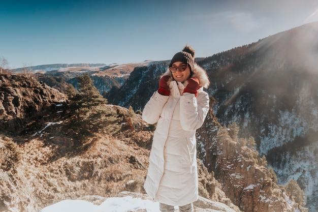 Portret van een positieve jonge vrouw in een de winter witte jas en hoed glimlacht