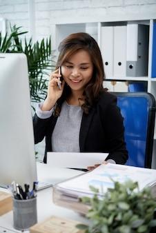 Portret van een positieve jonge zakenvrouw die telefoneert om de details van de overeenkomst te verduidelijken
