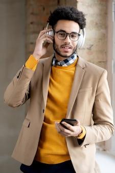 Portret van een positieve knappe jonge man van gemengd ras die smartphone gebruikt en draadloze hoofdtelefoons aanpast