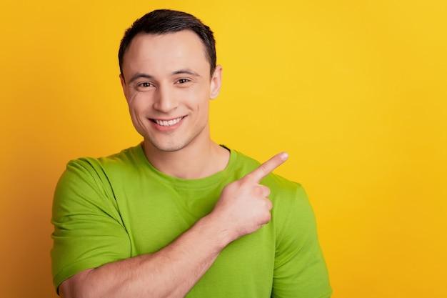 Portret van een positieve man geeft aan dat de lege ruimte van de wijsvinger nieuwigheid op gele achtergrond toont