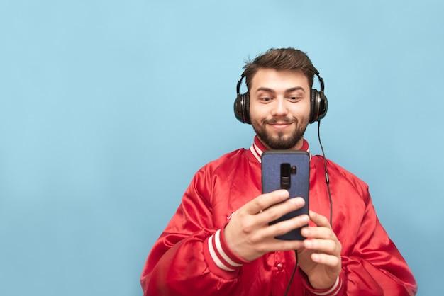 Portret van een positieve man met een baard, luistert naar muziek in koptelefoons en gebruikt een smartphone op blauw