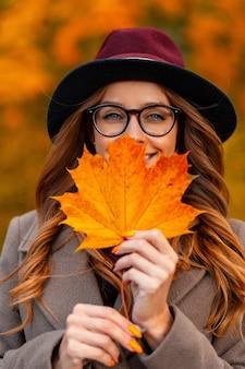 Portret van een positieve mooie jonge vrouw in een stijlvolle bril in een elegante bordeauxrode hoed in een herfstjas met een oranje blad in de buurt van gezicht in een park op een achtergrond van gouden gebladerte. blij meisje.