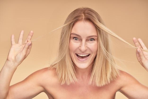 Portret van een positieve, mooie volwassen vrouw die met haar haar speelt en naar de camera glimlacht