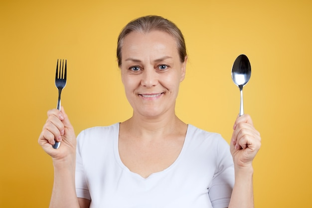 Portret van een positieve rijpe vrouw in een wit overhemd met een vork en lepel in haar handen
