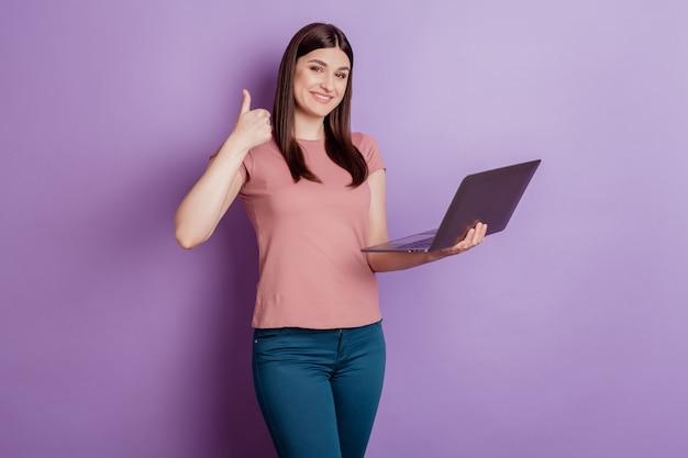 Portret van een positieve, succesvolle vrouw, een gelukkige positieve glimlach, toont een duim omhoog, zoals een laptop gebruiken die is geïsoleerd over een violette kleurachtergrond