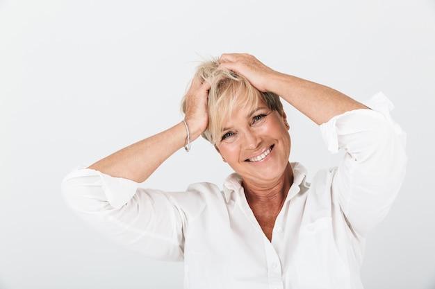 Portret van een positieve volwassen vrouw met kort blond haar die haar hoofd grijpt en lacht om de camera die over een witte muur in de studio wordt geïsoleerd