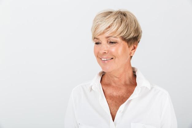 Portret van een positieve volwassen vrouw met kort blond haar die lacht naar de camera die over een witte muur in de studio wordt geïsoleerd