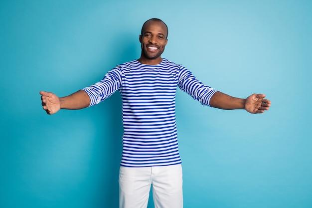 Portret van een positieve, vrolijke afro-amerikaanse man die ziet dat zijn vriend zijn handen openhoudt, wil knuffelen