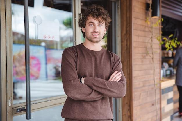 Portret van een positieve, vrolijke, gekrulde jongeman in een bruin sweetshirt met gekruiste armen