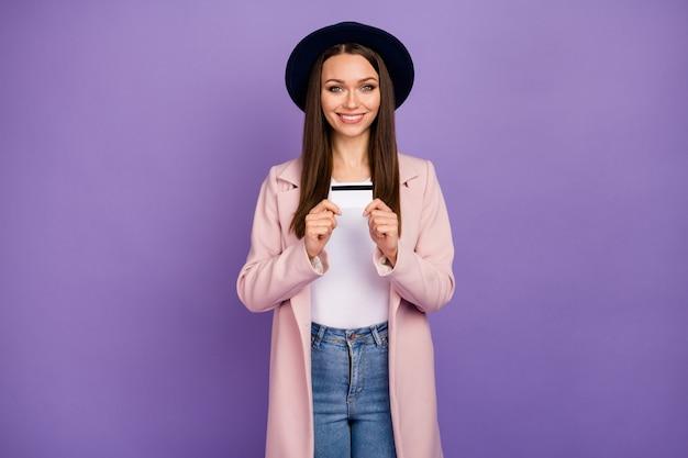 Portret van een positieve, vrolijke meid met een creditcard, raadt een eenvoudig bankbetalingssysteem aan, draag een goed uitziende pasteljas geïsoleerd over een violetkleurige achtergrond