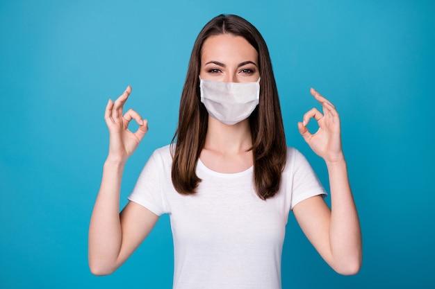 Portret van een positieve, vrolijke meisjespromotor die een goed teken toont, demonstreert covid-infectie, stop reclamepromotie, draag een medische maskeruitrusting geïsoleerd op een blauwe achtergrondkleur
