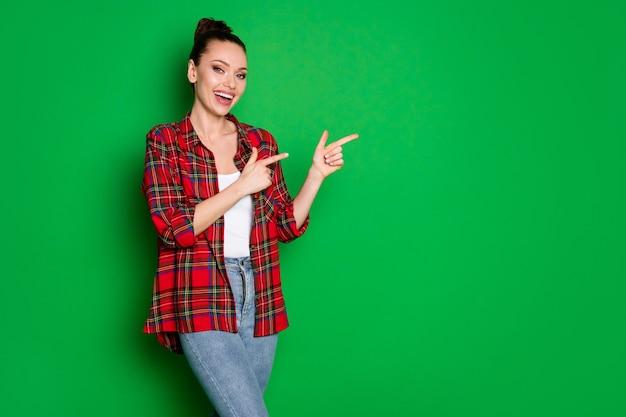 Portret van een positieve, vrolijke meisjespromotor geeft aan dat advertenties promotiepunt wijsvinger copyspace dragen denim jeans geïsoleerd glans kleur achtergrond