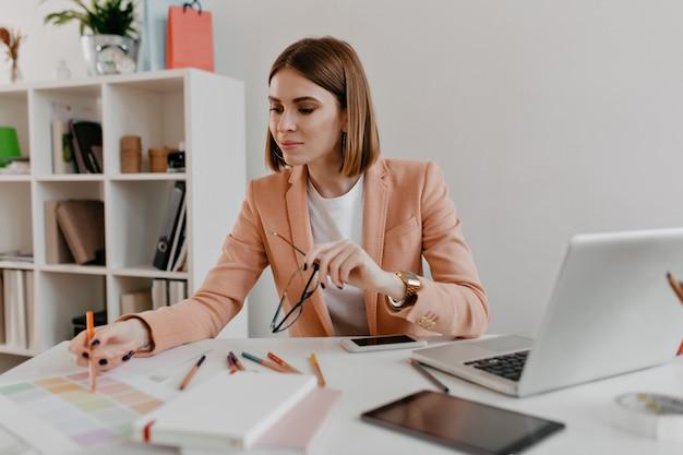 Portret van een positieve vrouw in een stijlvolle zakelijke outfit die met belangstelling naar documenten op haar bureaublad kijkt.