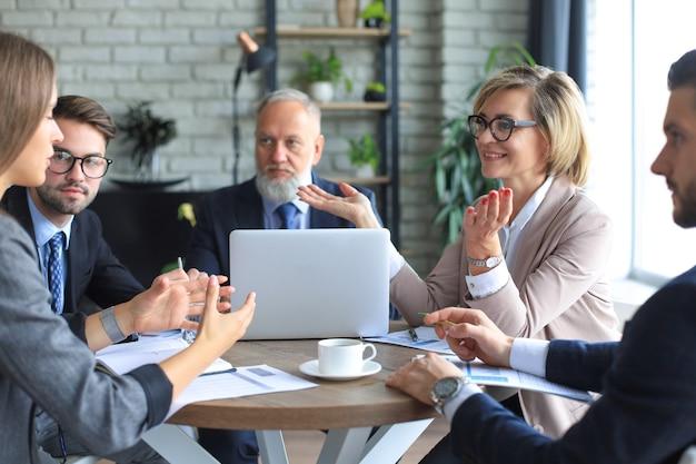 Portret van een positieve zakelijke medewerkers op een zakelijke bijeenkomst op kantoor.