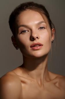Portret van een prachtig jong meisje met schone huid op donker