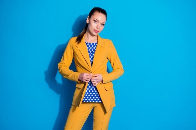 Portret van een prachtig, mooi hoofdmeisje, pas de knopblazer aan, bereid een zakelijke advocaatvergadering voor, draag een gele broek, een broek geïsoleerd over een blauwe achtergrondkleur