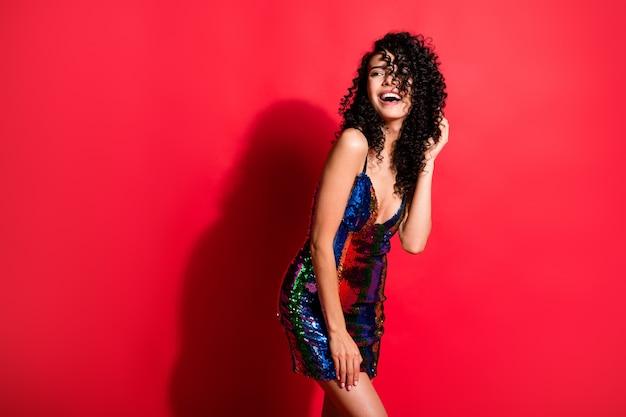 Portret van een prachtig vrolijk meisje met golvend haar dat een leuke disco-vrijgezellin heeft geïsoleerd op een heldere rode kleur achtergrond
