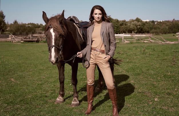 Portret van een prachtige brunette vrouw in een elegant geruit bruin jasje poseren met een paard op landlandschap