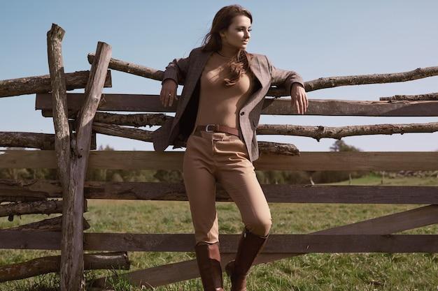 Portret van een prachtige brunette vrouw in een elegant geruit bruin jasje poseren op land landschap