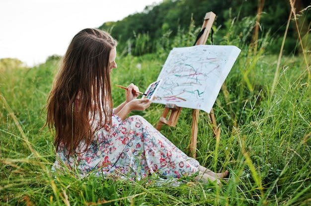 Portret van een prachtige gelukkige jonge vrouw in mooie jurk zittend op het gras en schilderen op papier met aquarellen.