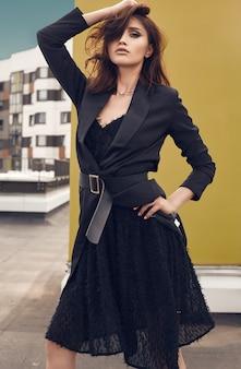 Portret van een prachtige heldere brunette vrouw in mode jurk die zich voordeed op het dak van een gebouw