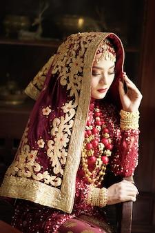 Portret van een prachtige indiase bruid in gouden en rode jurk