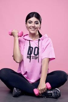 Portret van een prachtige lichaam positieve latijns-vrouw in een roze sport hoodie oefenen met halters op roze