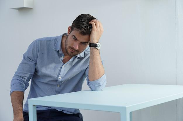 Portret van een prachtige man zittend in een wit ingerichte kamer met een lichtblauw klassiek overhemd