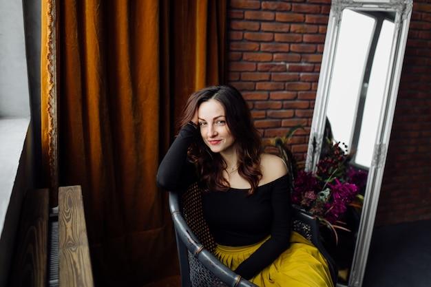 Portret van een prachtige modieuze vrouw, zittend in een stoel