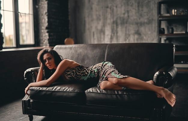 Portret van een prachtige mooie brunette met krullend haar, gekleed in een jurk die op een leren bank ligt en poseren, met mooie slanke benen.
