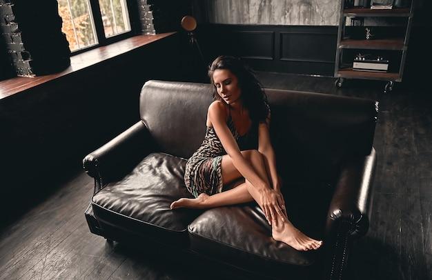 Portret van een prachtige mooie brunette met krullend haar, gekleed in een jurk die op een leren bank zit en vormt.