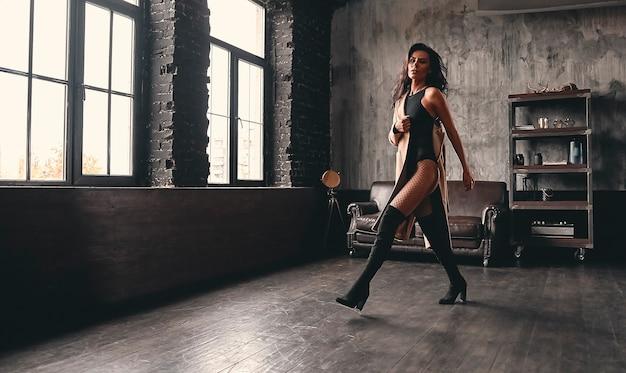 Portret van een prachtige mooie brunette met krullend haar in een jas en mesh panty's, in hoge zwarte laarzen onderweg poseren.