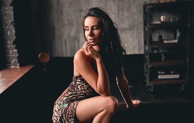 Portret van een prachtige mooie brunette met krullend haar in een jurk die in de buurt van een leren bank vormt.