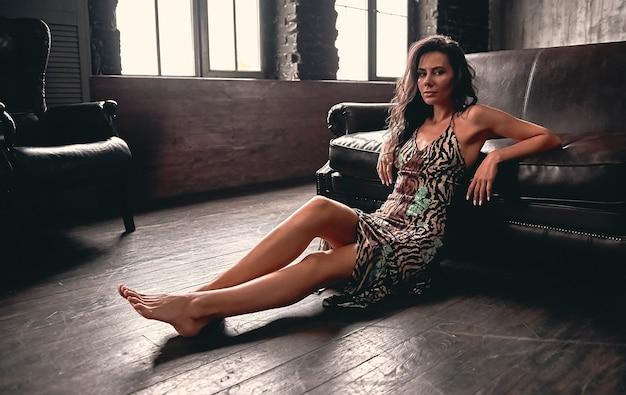 Portret van een prachtige mooie brunette met krullend haar in een jurk die op een houten vloer zit, leunend op een leren bank, met lange slanke benen.