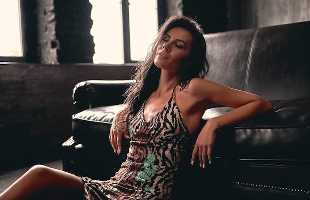 Portret van een prachtige mooie brunette met krullend haar in een jurk die op een houten vloer zit, leunend op een leren bank.