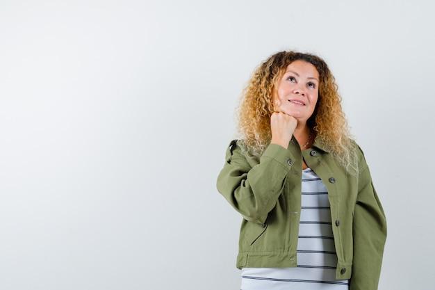 Portret van een prachtige vrouw die haar vuist onder de kin houdt in een groene jas, een shirt en een preoccupeerd vooraanzicht