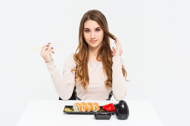 Portret van een prachtige vrouw die op een witte tafel zit en eetstokjes vasthoudt, geïsoleerd op een witte muur