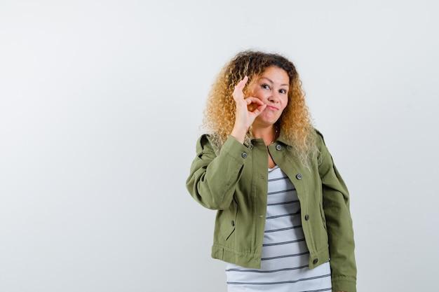 Portret van een prachtige vrouw die ritssluitinggebaar in groen jasje, overhemd toont en zorgvuldig vooraanzicht kijkt
