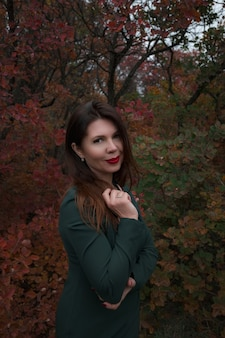 Portret van een prachtige vrouw van middelbare leeftijd in een herfstpark. hallo november. stijlvolle volwassen vrouw in een mooie jurk