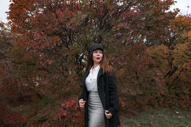 Portret van een prachtige vrouw van middelbare leeftijd in een herfstpark. hallo november. stijlvolle volwassen vrouw met een pet en zwarte jas