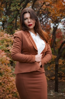Portret van een prachtige vrouw van middelbare leeftijd in een herfstpark. hallo november.