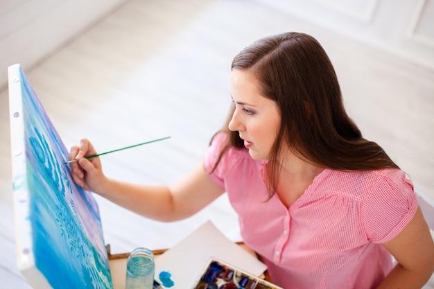 Portret van een prachtige vrouwelijke kunstenaar die werkt aan verschillende kunstprojecten in haar studio