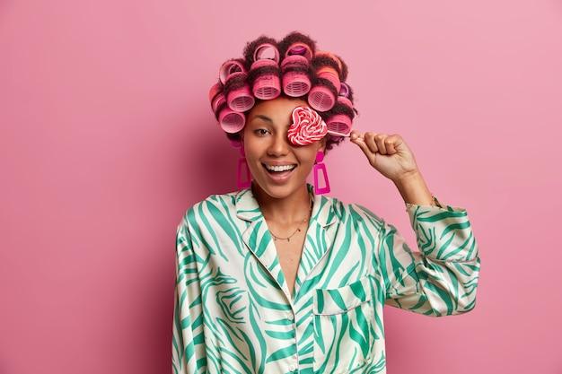 Portret van een prettig uitziende jonge vrouw met haarkrulspelden en een casual zijden kamerjas