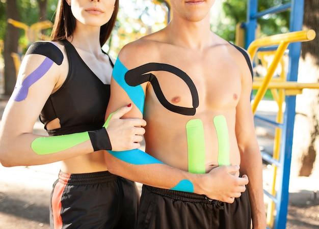 Portret van een professioneel kaukasisch atletenpaar, knappe man en brunette vrouw met kinesiologische tape op lichamen, poseren op sportveld, opzij kijkend. gezond levensstijlconcept.