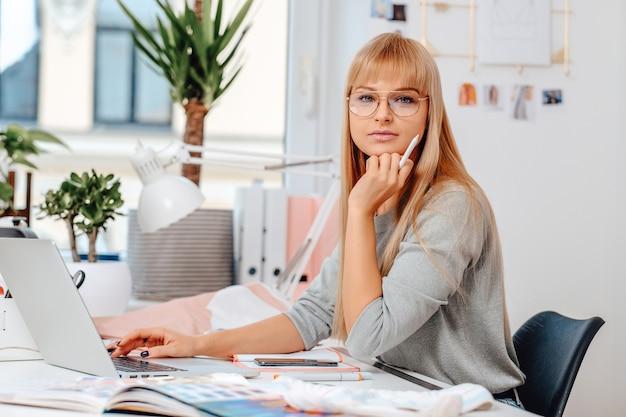 Portret van een professionele femnale ondernemer ze kijkt naar de camera. kaukasische vrouw op het werk. aantrekkelijke zakenvrouw zittend aan tafel met een laptop en een pen.