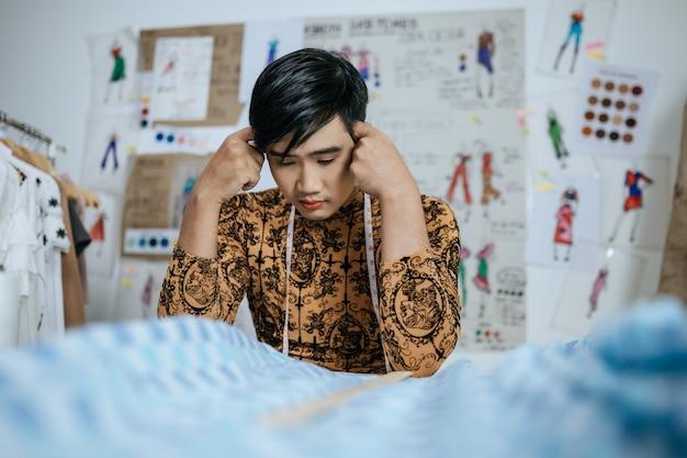 Portret van een professionele, gestresste aziatische jonge mannelijke kleermaker met een meetlint op de nek die het hoofd aanraakt met de handen in de studio.