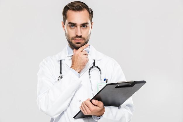 Portret van een professionele jonge arts die een gezondheidskaart vasthoudt die over een witte muur wordt geïsoleerd